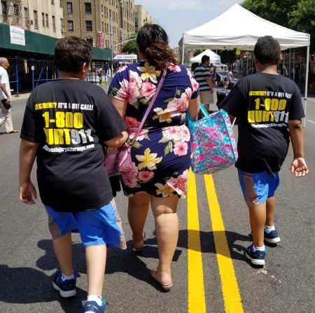 Two boys at the street fair wearing 1-800-HURT-911® T-shirts